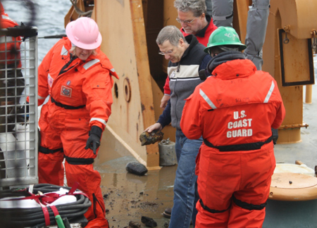 Larry Mayer observes the dredge on Healy's deck with Kelly Brumley and Bernie Coakley.