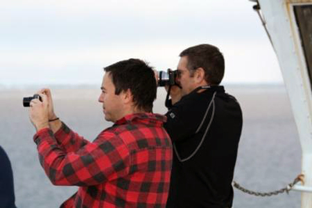 Roland Arsenault and John Farrel on the deck of the Healy taking photographs of a polar bear.