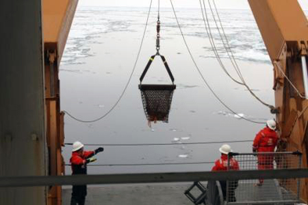 Suspended dredge bucket is guided aboard Healy over the stern.