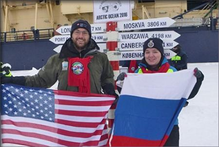 Kevin and Evgenia pose on the ice in front of the Oden holding US and Russian flags.