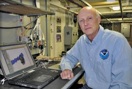 Andy Armstrong with laptop in a ship's lab space.