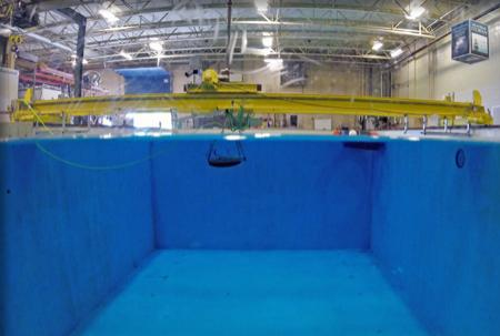 Photo of engineering tank at water level showing water below and the highbay above.