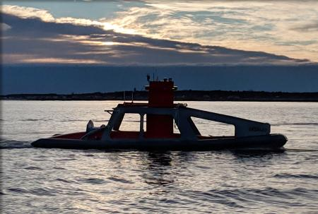 The DriX ASV in its docking platform on the water silhouetted against the evening sky.
