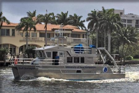 Aluminum, dual-hauled vessel cruising through Florida waters with large house and palm trees in the background.