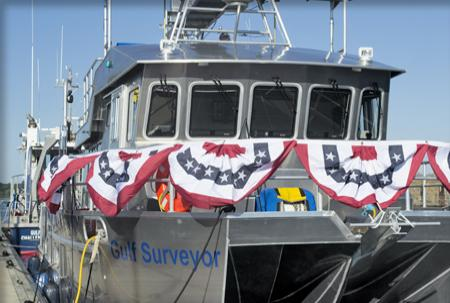 The bow of the Gulf Surveyor with red, white, and blue bunting on the railings.