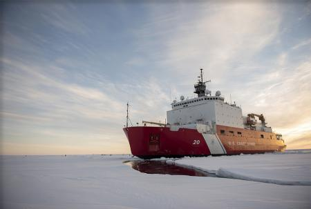 USCGC Healy in the ice  with dramatic clouds in the sky.