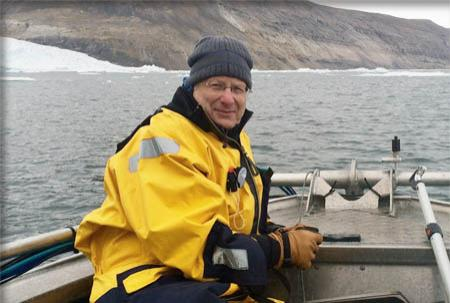 Larry Mayer in his yellow slicker sits in a launch boat in a Greenland fjord.