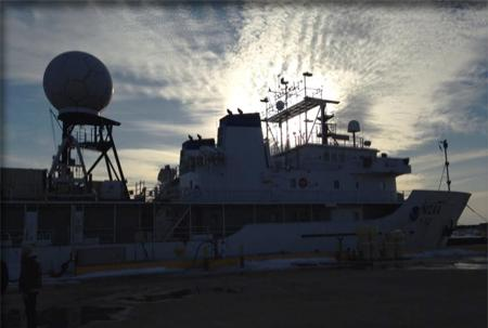 The Okeanos Explorer dockside, silhouetted against a lightening sky.