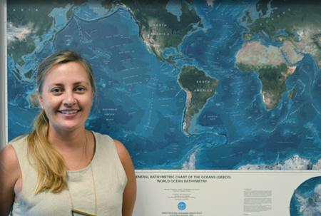 Headshot of Meme Lobeckers with GEBCO map of world oceans behind her.