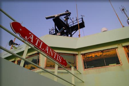 "Red placard reading, ""Atlantis,"" on a railing on the ship."