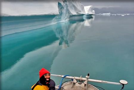 Side of iceberg reflected in the water; bow of survey vessel in foreground with grinning researcher.