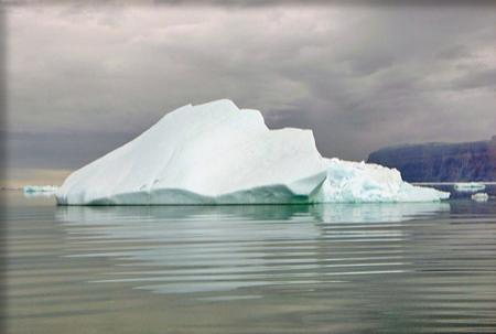An iceberg floats on calm water against a cloudy sky.