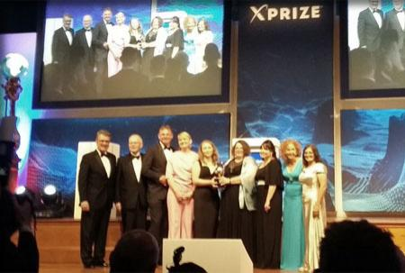 The team members gather on stage at the XPRIZE awards.