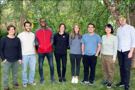 Group photo of eight new students outside in front of a backdrop of green trees.